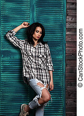 Beautiful makeup woman in trendy black and white checkered shirt, blue ripped jeans thinking and looking down on blue wooden doors background.