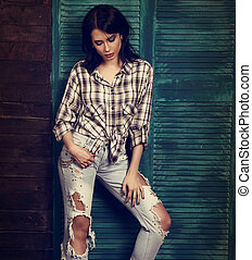 Beautiful makeup woman in trendy black and white checkered shirt, blue ripped jeans thinking and looking down on blue wooden background. Toned portrait
