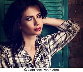 Beautiful makeup woman in trendy black and white checkered shirt looking relax and  thinking on blue wooden doors background. Short hairstyle. Closeup contrast toned portrait