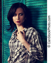 Beautiful makeup woman in trendy black and white checkered shirt looking with fear emotion on wooden background. Short hairstyle. Contrast closeup portrait. Toned