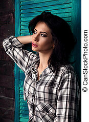 Beautiful makeup woman in trendy black and white checkered shirt thinking on blue wooden background. Short hairstyle