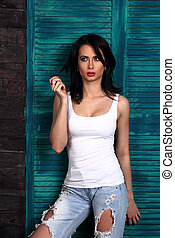 Beautiful makeup woman in trendy white casual top, blue ripped jeans thinking and looking on blue wooden background.