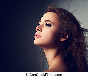 Beautiful makeup woman profile with long hair looking up with hope on light