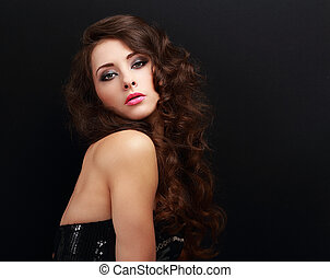 Beautiful makeup woman with brown long curly hair on black