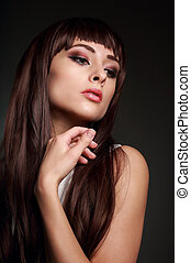 Beautiful makeup woman with brown long shiny hair on dark background