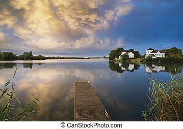 Beautiful mammatus clouds forming over lake landscape...