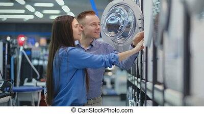 Beautiful man and woman choose modern smart washing machine...