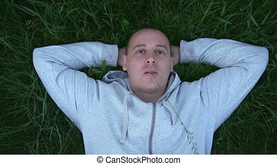 Beautiful man is lying on the grass holding a grass in his mouth. slow motion