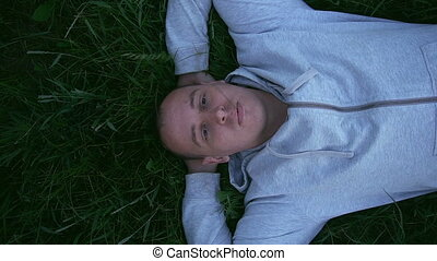 Beautiful man is lying on the grass holding a grass in his...