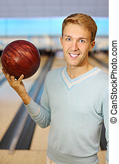 Beautiful man wearing in blue poluver holds red ball in ...