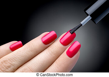 Beautiful manicure process. Nail polish being applied to hand, polish is a red color. Black background closeup.