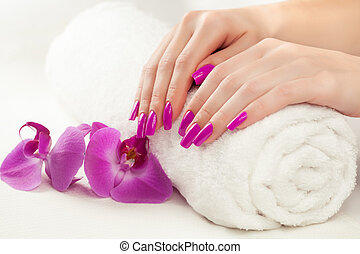 beautiful manicure with pink orchid and towel - female hands...