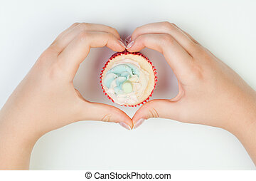 Beautiful manicured woman's nails holding cake. Hands in shape heart