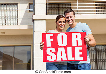 married couple outside home holding for sale sign