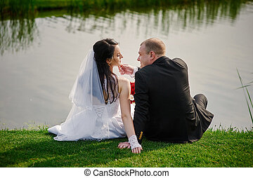 Beautiful married couple sitting on river bank in summer