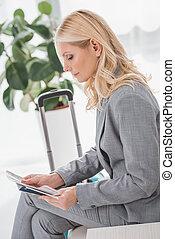 businesswoman looking at flight ticket