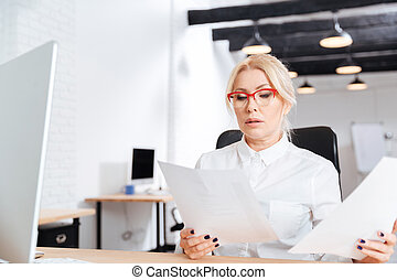 Beautiful mature businesswoman reading papers