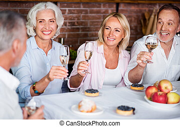 Beautiful mature family toasting with white wine