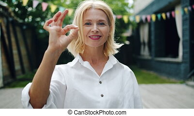 Beautiful mature lady showing OK hand gesture and smiling...