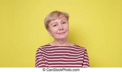 Beautiful mature lady with a lively smile looking directly at the camera. Studio shot on yellow wall.