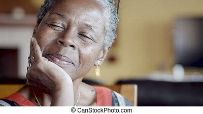 Beautiful mature senior African American woman nodding and...