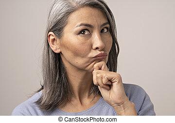 Beautiful mature woman blows lips while touching her chin