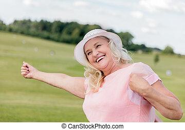 Beautiful mature woman dancing in the field.