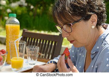 beautiful mature woman eating  strawberry, outside