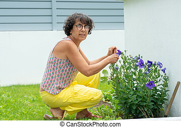 Beautiful mature woman in a garden with flowers