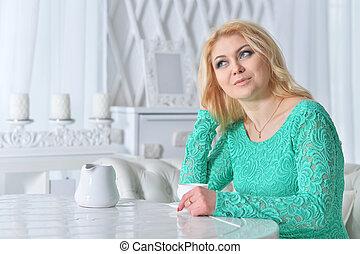 Beautiful mature woman in green dress drinking tea