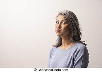 Beautiful mature woman is making funny faces