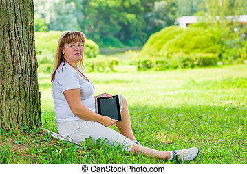 beautiful mature woman near a tree in the park with tablet