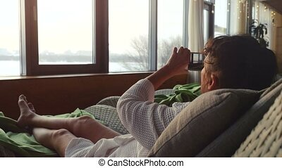 Beautiful mature woman relaxing in spa and taking picture from her smart phone lying on the sofa and looks sunset from the window. 3840x2160. 4k