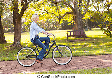 mature woman riding a bike at the park
