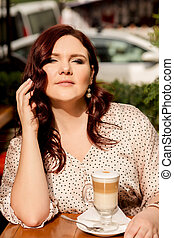 Beautiful mature woman sitting at a street cafe with a cup of coffee in a sunny evening