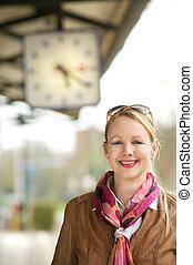 Beautiful mature woman smiling under train station clock -...