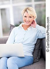 beautiful mature woman using laptop at home