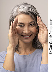 Beautiful mature woman with hands at face