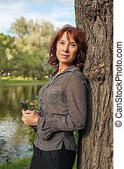 Beautiful mature woman with smartphone resting outdoors. Woman cell phone