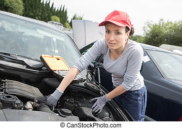 beautiful mechanic woman working on a car