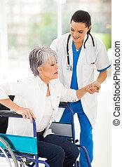medical nurse helping senior woman on wheelchair