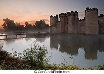Beautiful medieval castle and moat at sunrise with mist over moat and sunlight behind castle