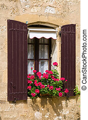 Window with shutters and window box, photographed in the Dordogne region of France
