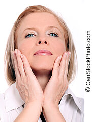Beautiful mid aged woman touching her face on a white...