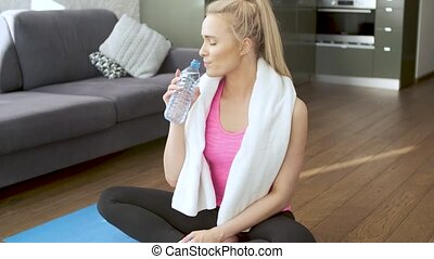 Beautiful middle age blond female wiping sweat with towel after physical workout
