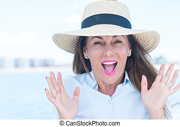 Beautiful middle age woman traveling on sailboat scared in shock with a surprise face, afraid and excited with fear expression