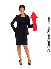 middle aged african woman holding red arrow pointing up