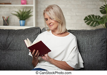Beautiful middle aged blonde woman is reading a book at home