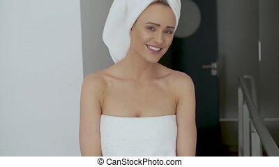 Beautiful middle aged blonde woman wrapped in towel white...