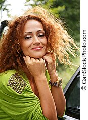 Beautiful middle-aged redhead smiling woman outdoors